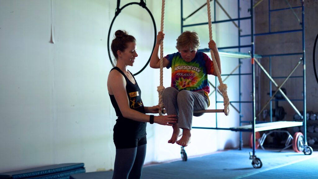 Young student on trapeze with instructor nearby.